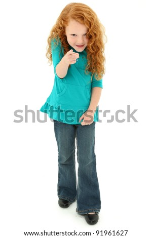 Adorable young preschool girl child pointing playfully towards the camera over white background.