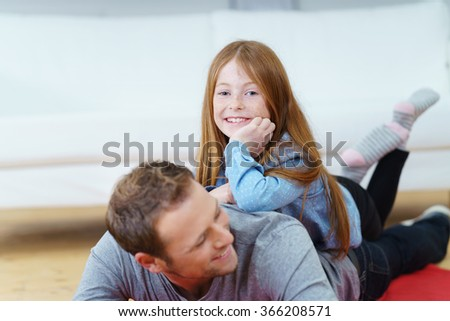 Adorable young redhead girl with her father playing on the floor of the living room at home as she rides on his back while smiling at the camera - stock photo
