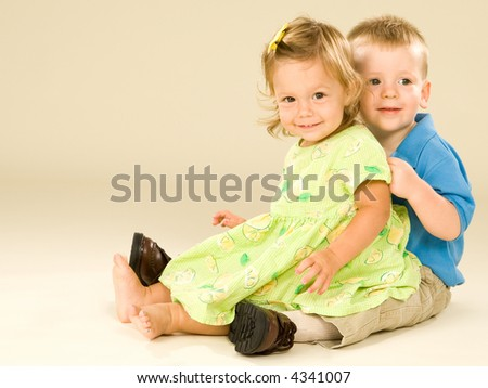 Adorable young toddler boy and baby girl embrace and display authentic happy smiles. - stock photo