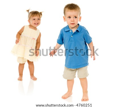 Adorable young toddler boy and baby looking to camera right. Happy but curious, quizzical expressions. Isolated on white.