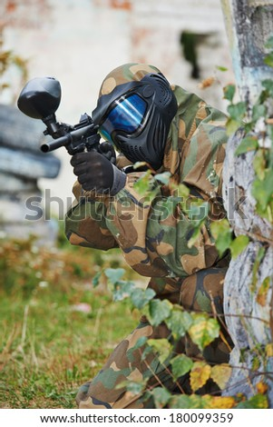 Adrenalin paintball player in protective uniform and mask aiming gun before shooting in summer