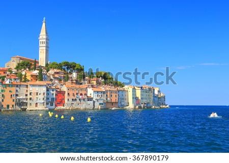 Adriatic sea and distant buildings of an old Venetian town, Rovinj, Croatia - stock photo