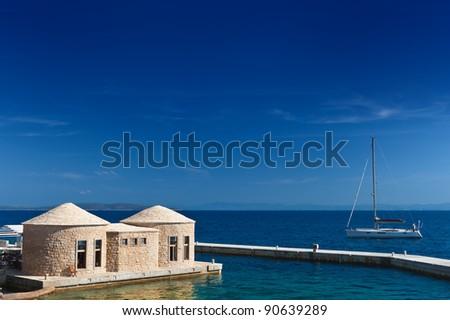 Adriatic sea coast of Croatia. Scenic view with yacht and typical Dalmatian styled stoned huts: bunja (trim, kazun). Hvar island. - stock photo