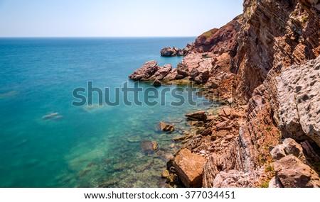 Adriatic sea coastline with red rocks and blurred sea water. Long exposure photo, Sutomore, Montenegro. - stock photo