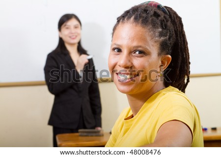 adult african student in classroom, background is a teacher standing in front of white board - stock photo