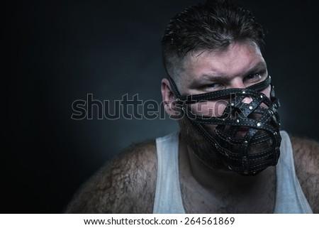 Adult agressive man in muzzle in the dark - stock photo