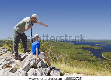 Adult and child standing on a mountaintop near the Arkansas River. Father, leaning on his stick, shows his son the sights - stock photo