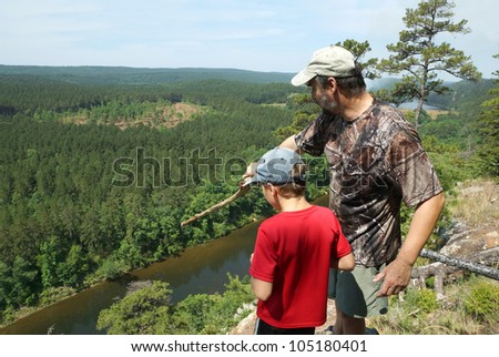 Adult and child standing on a mountaintop near the Arkansas River. The father shows his son the sights - stock photo