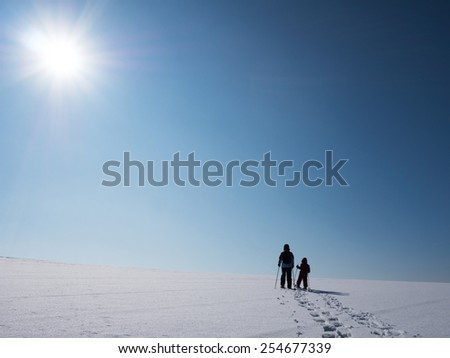 Adult and kid snowshoeing in the sunlight - stock photo
