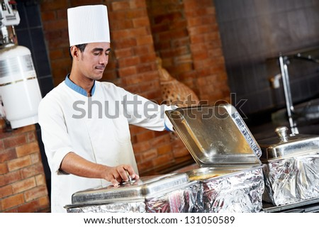 Adult arab chef man in uniform demonstrating food on cooker in resort hotel restaurant kitchen - stock photo