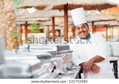 Adult arab chef man in uniform with food on cooker in resort hotel restaurant kitchen - stock photo