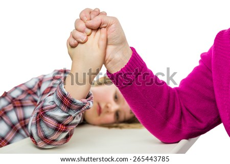 Adult arm wrestling with young girl. Arm-wrestling as concept of play, fight, force, pressure, game, relation,relationship, elder, child. The girl lies with her head on the table looking under the arm - stock photo