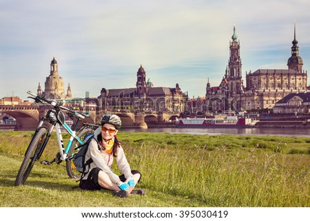 Adult attractive female cyclist sitting  on the grass and resting. The happy woman sits  at the old city background and  looks at the camera. So-called  The Balcony of Europe, Dresden, Germany - stock photo