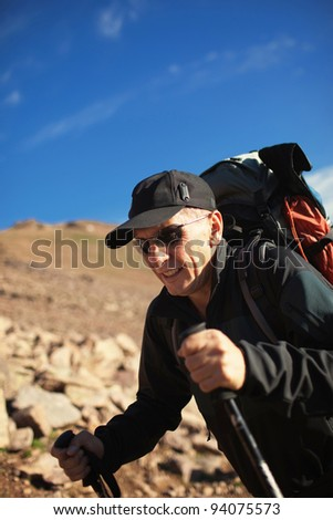 Adult backpacker in the mountains - stock photo