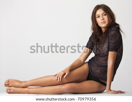 adult beautiful sensual brunette sitting on a gray background isolated picture - stock photo