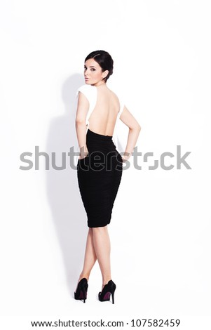 adult beautiful woman in elegant black and white dress back view studio white - stock photo