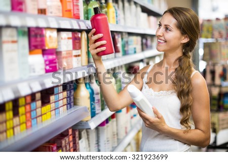 Adult beautiful woman in good spirits selecting shampoo in a store  - stock photo