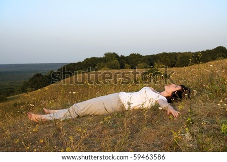 Adult, beautiful woman, who concerns with the yoga, on sundown of the day. - stock photo