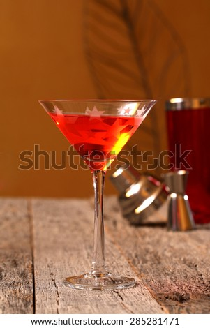 Adult beverage Cosmo colorful drink in martini glass on weathered, rustic tabletop  - stock photo