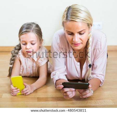 Adult blonde and little girl looking at screens of smartphones indoors. Focus on woman