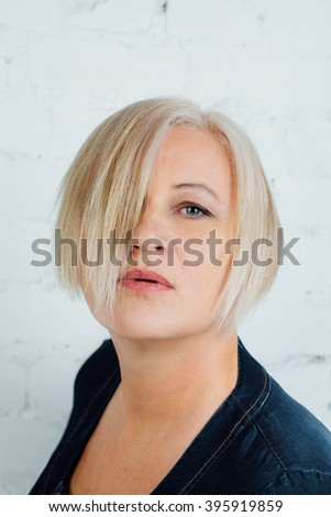 Adult blonde woman in jeans dress. Against the background of a white brick wall. Quiet, looking into the frame. Part of Face covered with hair. parted lips