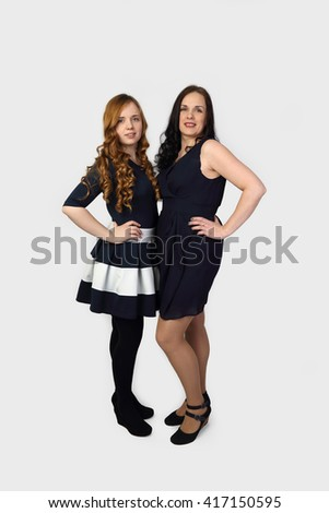Adult brunette woman and young redhead girl stand full height on gray background - Mother and daughter portrait