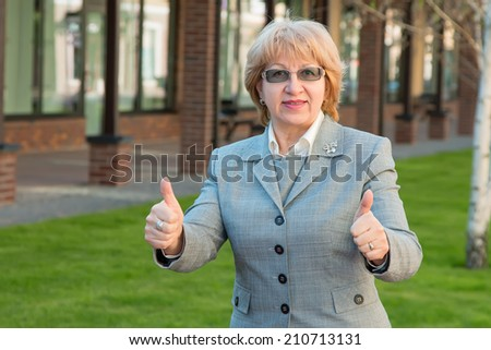 Adult business woman. Woman head small businesses. Portrait of a modern woman experienced leader. Adult woman of retirement age in the glasses. Happy smiling business woman with thumbs up gesture. - stock photo