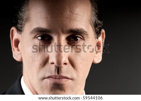 Adult businessman closeup portrait on dark background. - stock photo