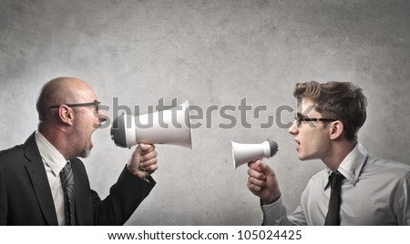 Adult businessman screaming into a megaphone against a younger businessman talking into a smaller one - stock photo