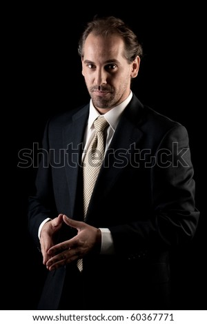 Adult businessman serious hands gesture on black background - stock photo