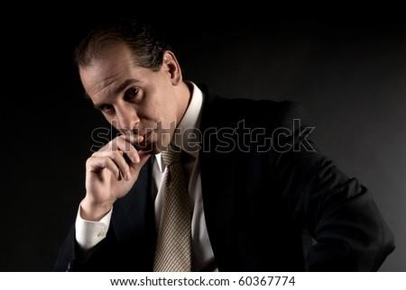 adult businessman serious thinking sitting on dark background - stock photo