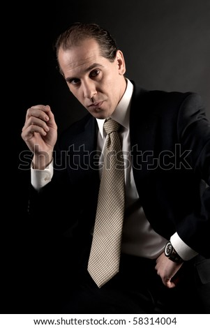 adult businessman welldressed serious sitting looking at camera. - stock photo