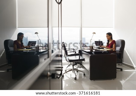 Adult businesswoman sitting in modern office in skyscraper. The secretary is concentrated and writes email on tablet computer. Wide shot - stock photo
