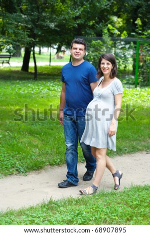 Adult caucasian couple walking in park, sport helps pregnancy - stock photo
