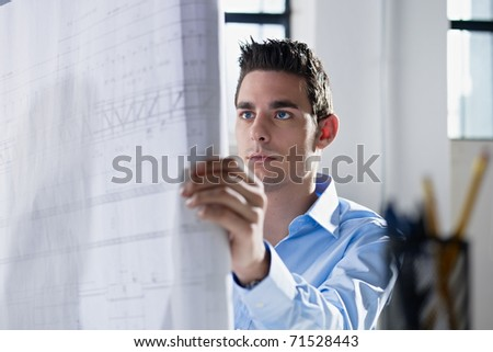 adult caucasian male architect examining blueprints. Horizontal shape, head and shoulders, side view - stock photo