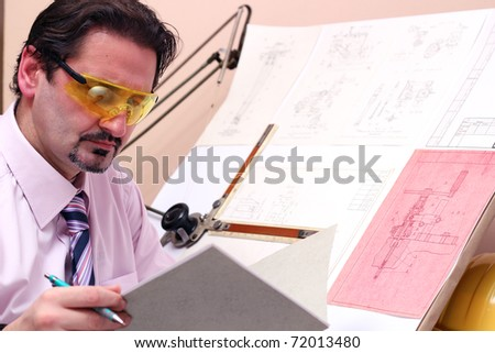 Adult caucasian male engineer examining documents. Focus on face. - stock photo