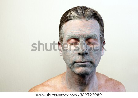 Adult caucasian male with eyes closed wearing a drying green bentonite clay facial mask. Front of white guy with a cracking and almost dry face beauty mask of bentonite clay.