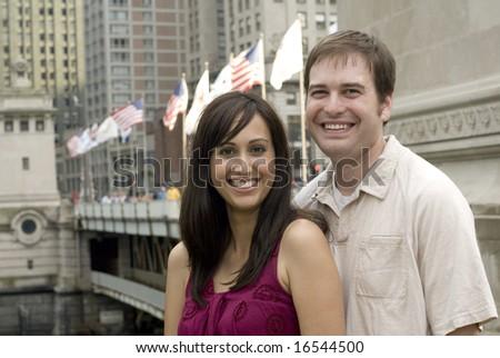Adult Caucasian man and woman smiling near bridge. - stock photo