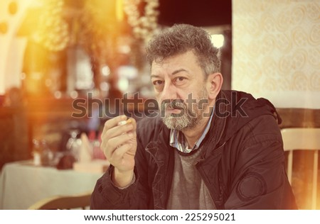Adult caucasian man with beard smoking cigarette vintage look of photo  - stock photo