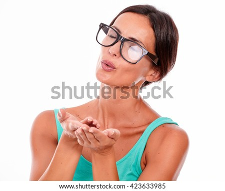 Adult caucasian woman blowing a kiss with her eyes closed while wishing and gesturing with her hands on a white background - stock photo