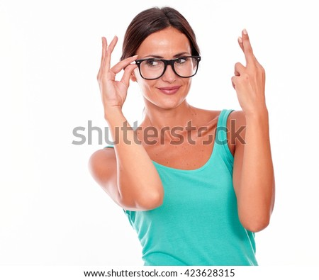 Adult caucasian woman crossing her fingers while looking away and touching her glasses wishing on a white background - stock photo