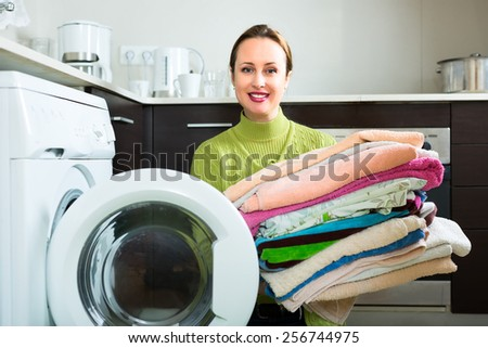 Adult caucasian woman in green warm sweater sitting on her knees near washing machine doing laundry - stock photo