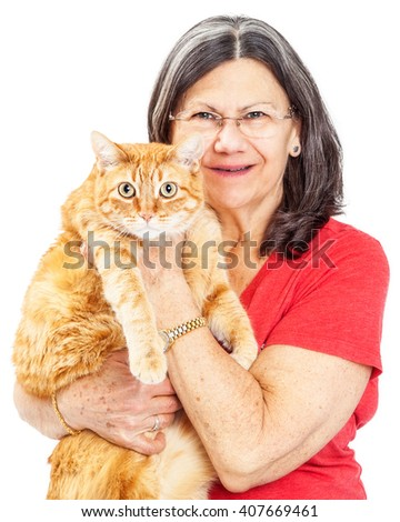 Adult caucasian woman with grey hair holding a big orange tabby cat - stock photo