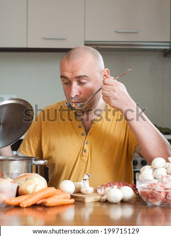 Adult chef prepares a dish of meat - stock photo