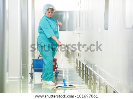 Adult cleaner maid woman with mop and uniform cleaning corridor pass floor of pharmacy industry factory or clinic - stock photo