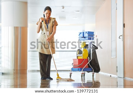 Adult cleaner maid woman with mop and uniform cleaning corridor pass or hall floor of business building
