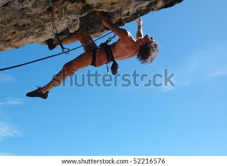 Adult climbing hard overhanging rock. - stock photo
