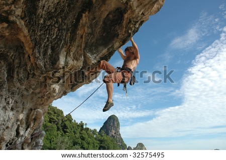 Adult climbing hard overhanging wall in Krabi, Thailand.