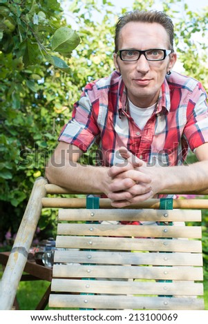 Adult confident young man smile and lean the lounger in his garden, looking into camera. copy space bottom - stock photo