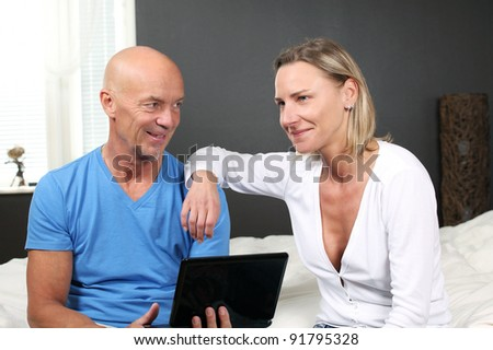 Adult couple at home discussing online services in relaxed pose sitting on bed